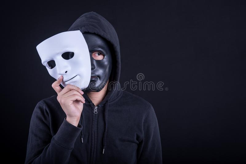 Mystery man wearing black mask holding white mask. Anonymous social masking or halloween concept royalty free stock photo
