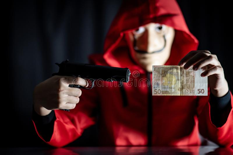 Mystery man holding gun and euro banknote stock photography