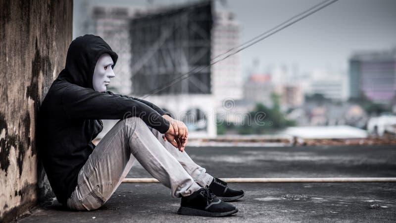 Mystery man in white mask feeling sad and depressed. Mystery man in white mask with hoody jacket, sitting thinking of something with sad eyes. depression self stock photography