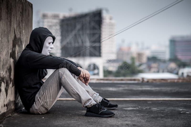 Mystery man in white mask feeling sad and depressed. Mystery man in white mask with hoody jacket, sitting thinking of something with sad eyes. depression self royalty free stock photos