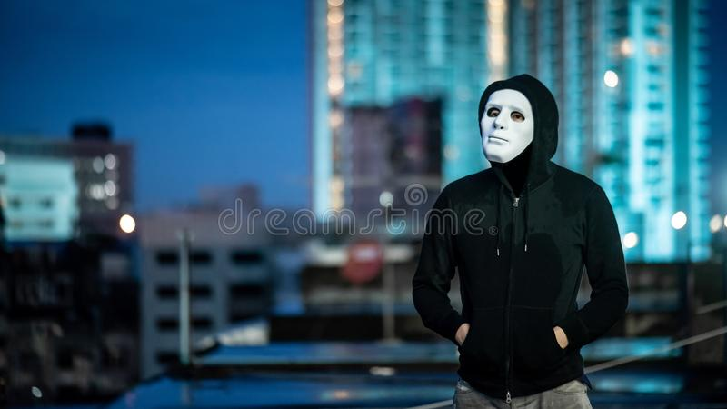 Mystery man in white mask standing on rooftop. Mystery hoodie man in white mask. standing on rooftop of abandoned building during the twilight . Biar disorder or stock image