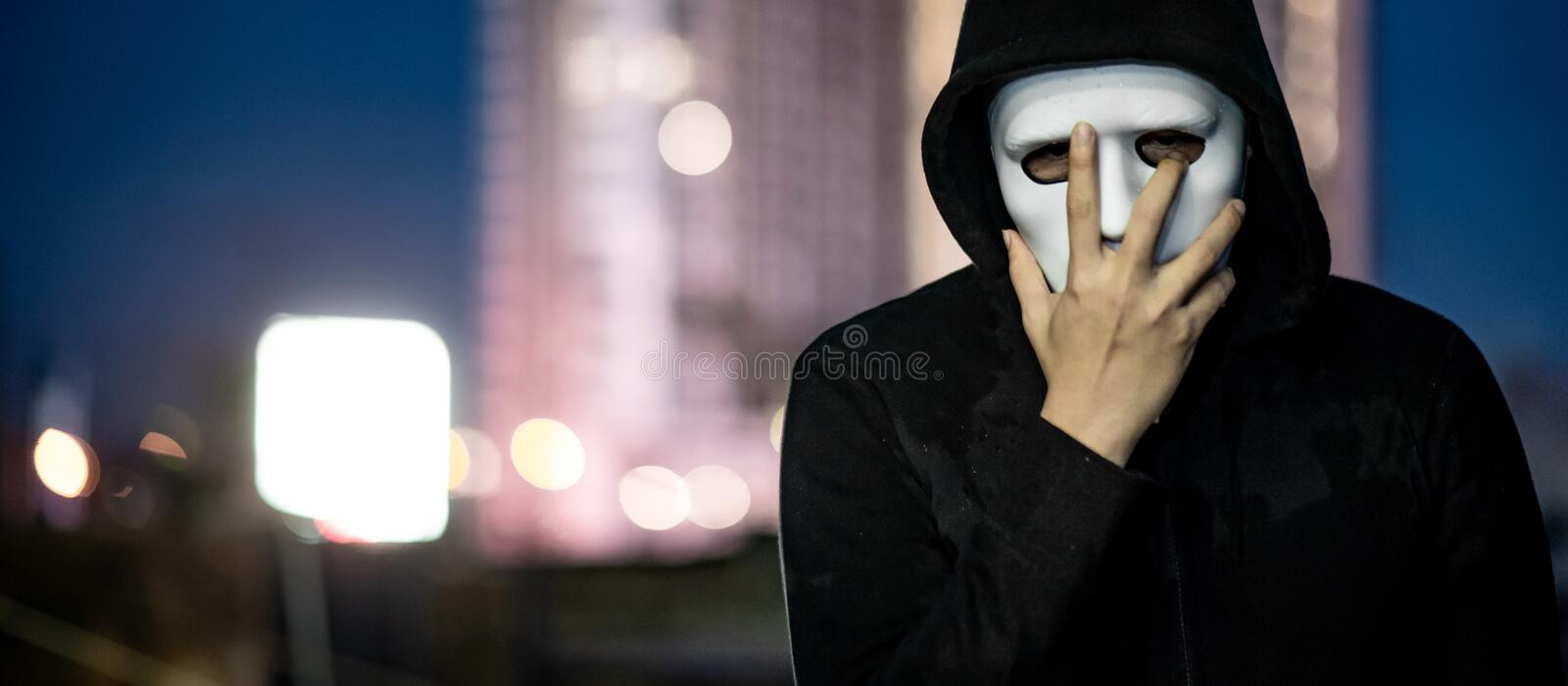 Mystery man in white mask standing on rooftop. Mystery hoodie man in white mask. standing on rooftop of abandoned building during the twilight . Biar disorder or stock images
