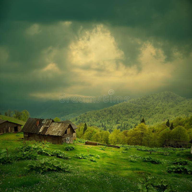 Mystery mountain landscape. Ray of light in dark clouds over the old wooden shack in green valley stock photos