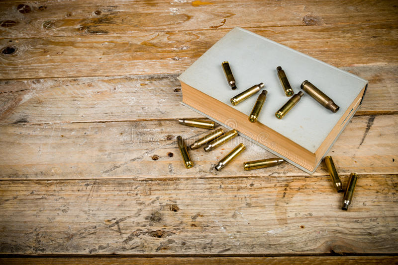 Mystery novels. Still life with old book and bullets, a mystery novel concept stock photography