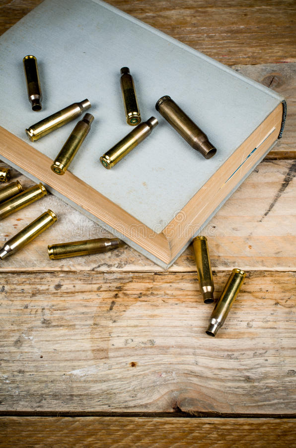 Mystery novels. Still life with old book and bullets, a mystery novel concept royalty free stock image