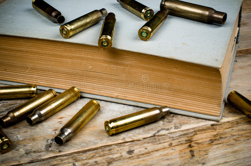 Mystery novels. Still life with old book and bullets, a mystery novel concept royalty free stock images
