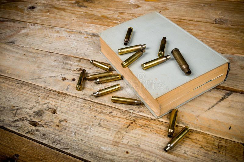 Mystery novels. Still life with old book and bullets, a mystery novel concept stock image