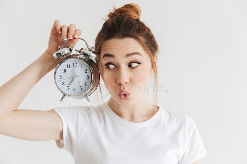 Mystery woman in casual clothes holing alarm clock stock photos