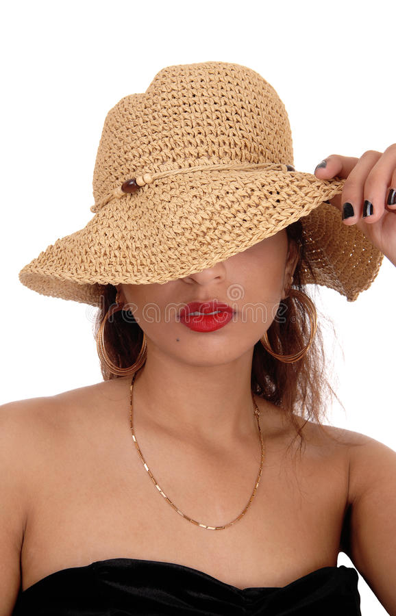 Mystery woman with straw hat. A beautiful mysterious woman with her straw hat over her face in a black dress and red lips, isolated for white background royalty free stock image