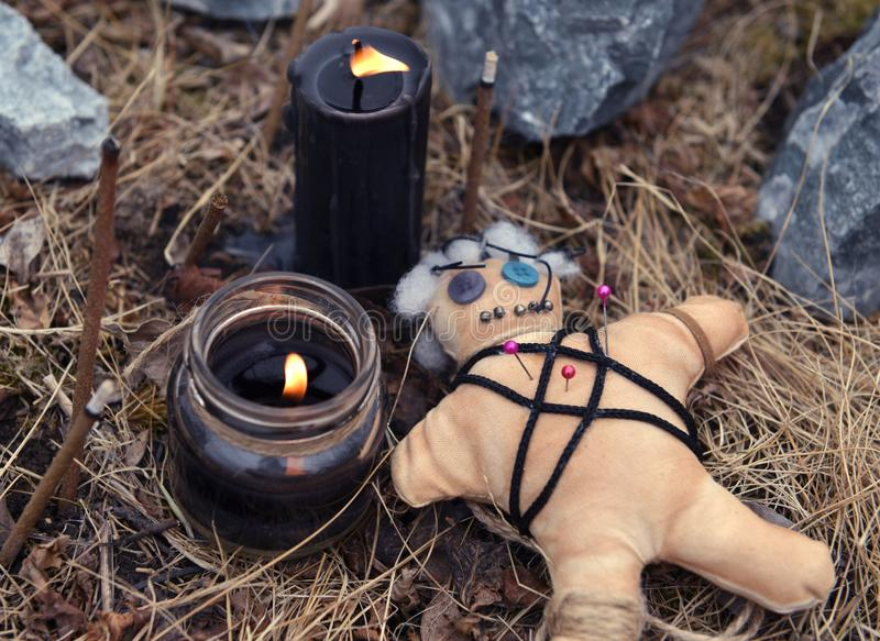 Voodoo doll with burning black candles and incense sticks among stones stock photos