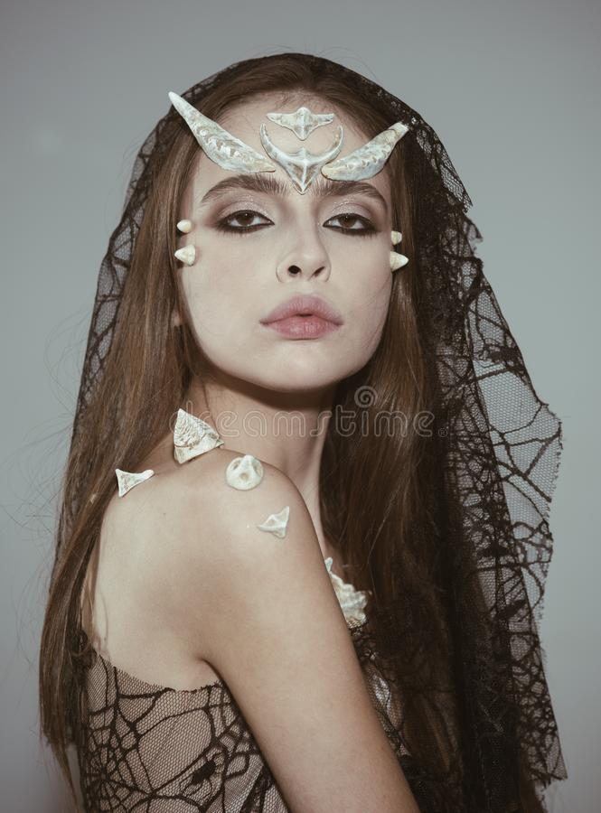 Mystic fairy tail character. Woman with horns and thorns wears black veil fantasy creature. Girl with fantasy style make. Up. Halloween ideas concept. Girl with stock photos