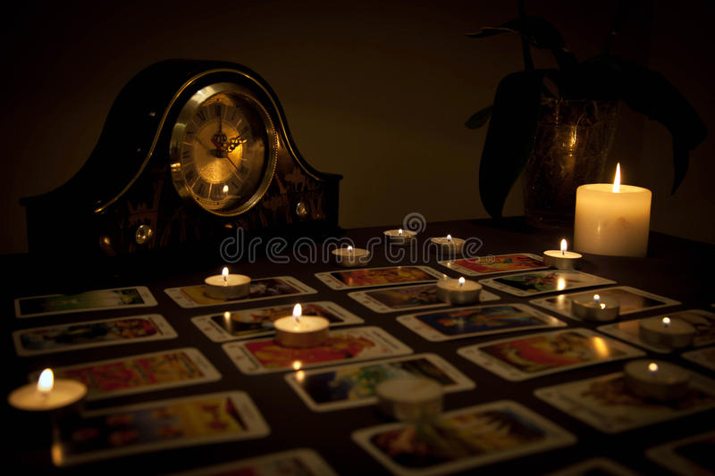 Mystic fortune-telling with fired candles and playing cards in d royalty free stock image