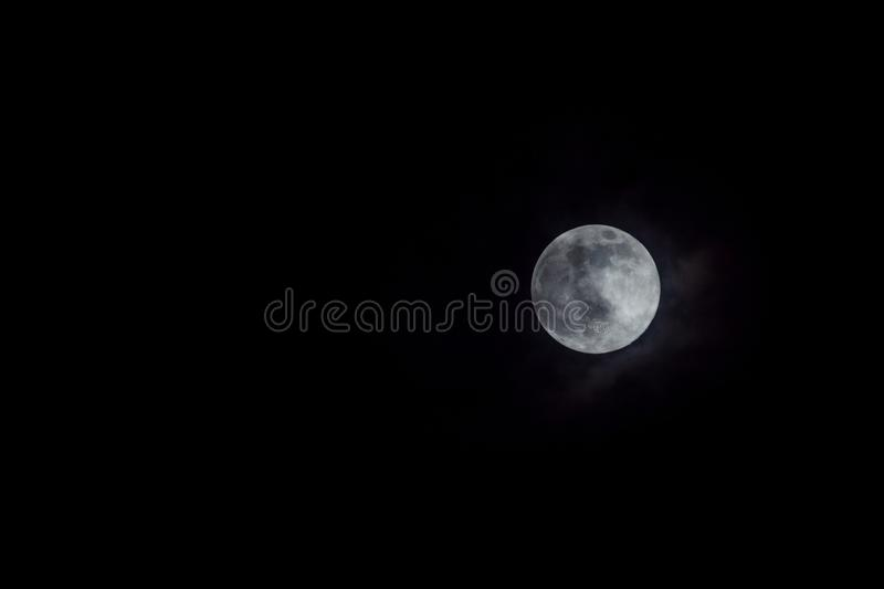 Mystic full moon in night sky with clouds stock images