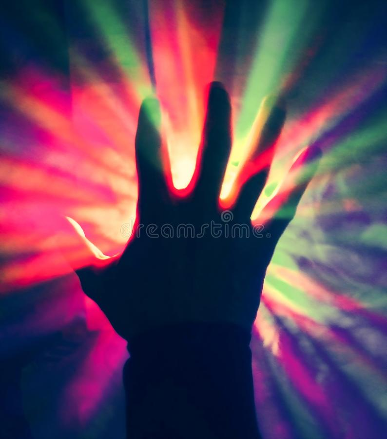 Mystic hand of a wizard throwing colorful rays of light stock photo