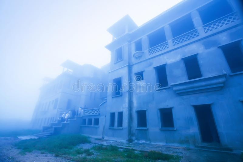 Mystic landscape of old French colonial building in the mist, old abandoned unfinished building of Bokor Casino, Borkor Mountain, stock photo
