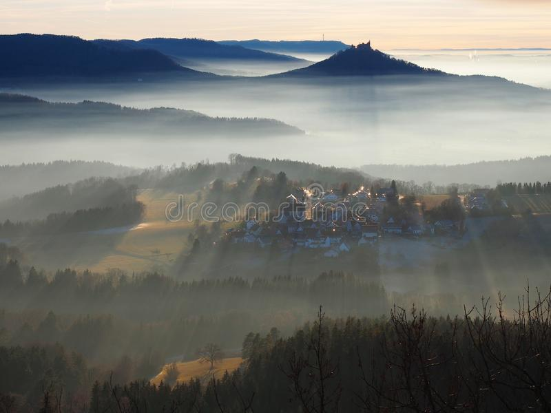 Mystic moments in the Swabian Alb. In Germany. Fog in the lowlands, fine weather at higher elevations. Shortly before sunset, the sun creates long, linear lines stock images