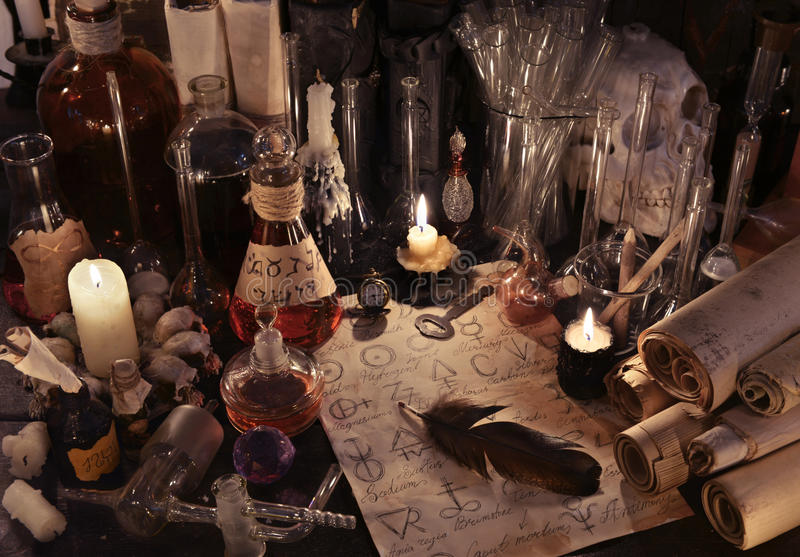 Mystic still life with alchemy paper, vintage bottles, candles and magic objects royalty free stock images
