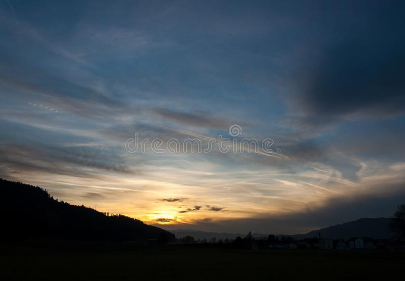 Mystic sunset in the austrian alps with mighty clouds in front of the sun royalty free stock photos