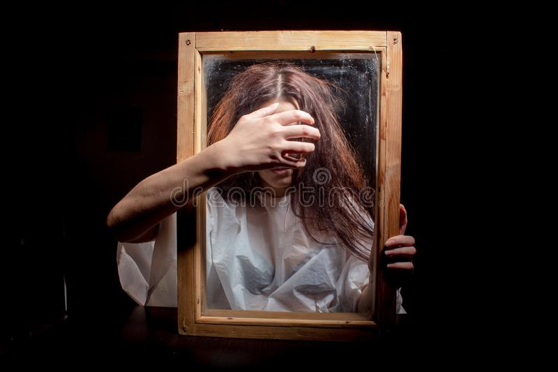 A mystical and frightening portrait of a girl looking through a frame. Hands with outstretched fingers in front. A mystical and frightening Studio portrait of a royalty free stock image