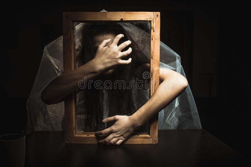 A mystical and frightening portrait of a girl looking through a frame. Hands with outstretched fingers in front. A mystical and frightening Studio portrait of a royalty free stock photography