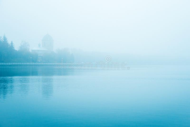 Mystical landscape with the old church above the lake in the misty morning in Ternopil, Ukraine.  stock photo