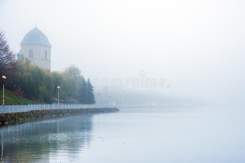 Mystical landscape with the old church above the lake in the misty morning in Ternopil, Ukraine.  royalty free stock image