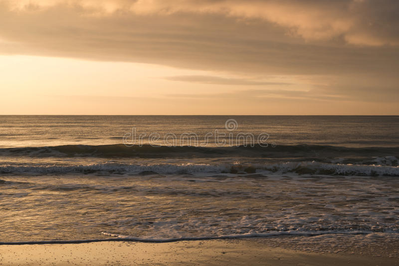 Mystical morning sunrise with a beautiful cloudy sky. On the beach stock photography