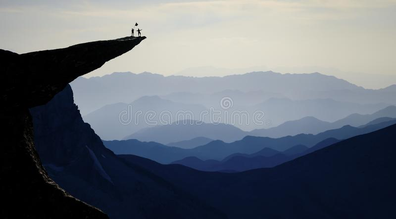Mountaineering team on rocky cliff. A pair of adventurers standing on a rocky cliff on mountain landscape stock photo
