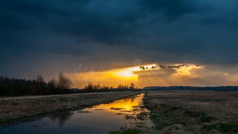 Mystical sunset. sunshine light the earth because of dark clouds. Spring mystical sunset. sunshine light the earth and the river because of dark clouds stock images