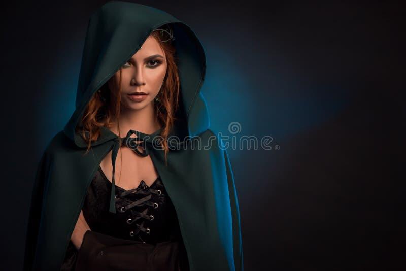 Mysticusmeisje het stellen op donkere achtergrond, die groene kaap, zwart korset dragen royalty-vrije stock afbeeldingen