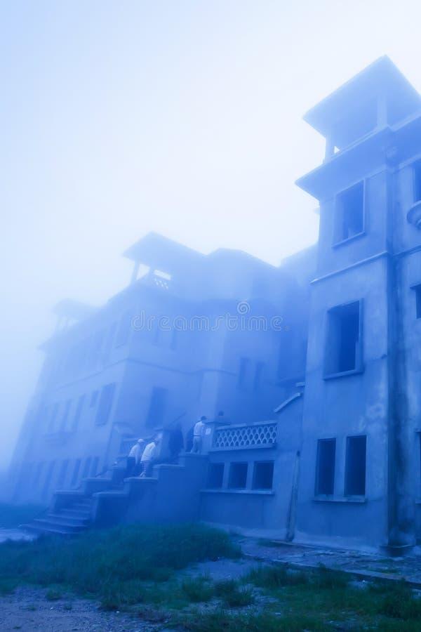 Mystikerlandskap av gammal fransk kolonial byggnad i misten, gammal övergiven oavslutad byggnad av den Bokor kasinot, Borkor berg arkivbilder
