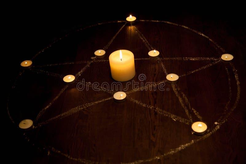 Mystikerpentagram med avfyrade stearinljus i mörker, på träbakgrund royaltyfria bilder