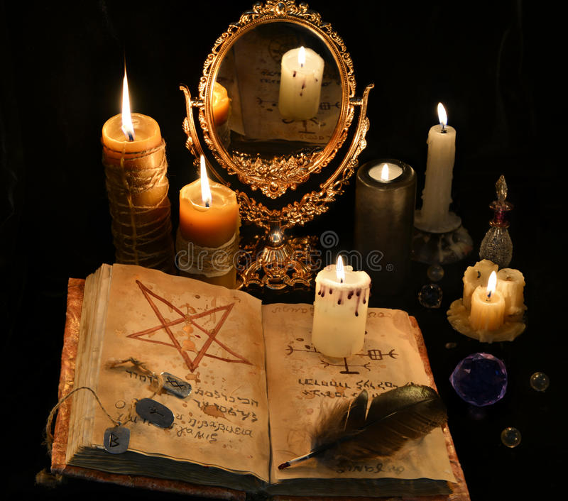 Mystikerstilleben med boken, stearinljus och mirrow för svart magi royaltyfri foto