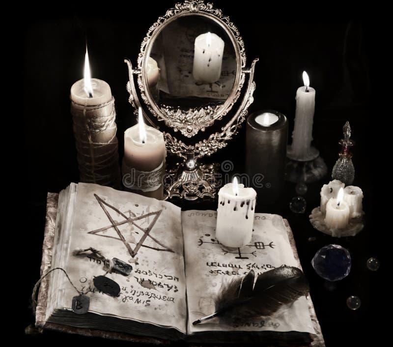 Mystikerstilleben med boken, stearinljus och mirrow för svart magi arkivbilder