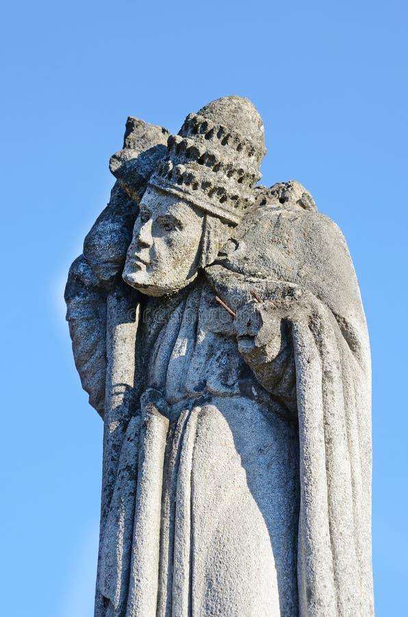 Mystische alte Steinstatue mit gerolltem wegkopf auf dem Grundstein I lizenzfreie stockfotografie