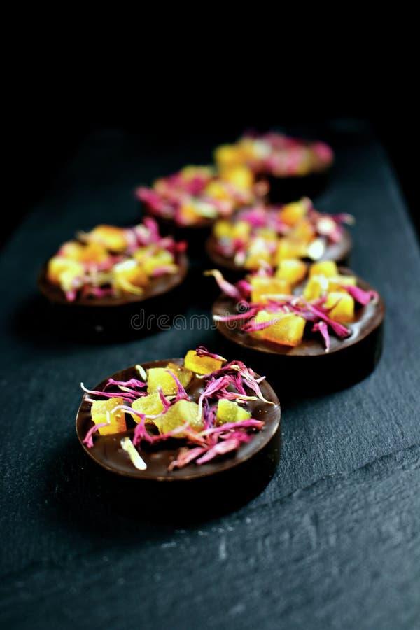 Mystische dunkle Schokoladenpralinen mit den kandierten orange und roten Flockenblumenblumenblättern auf dunklem Hintergrund stockbild
