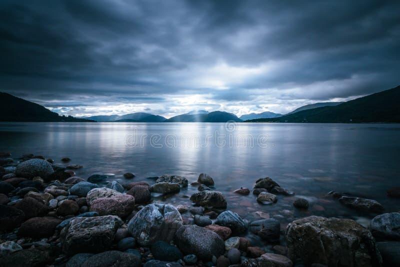Mystische Landschaftsseelandschaft in Schottland: Bewölkter Himmel, Sonnenstrahlen und Gebirgszug im Loch Linnhe lizenzfreies stockbild