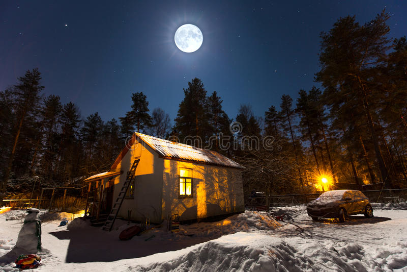 Mystisches Dorfhaus bedeckt mit Schnee im Mondschein stockfotos