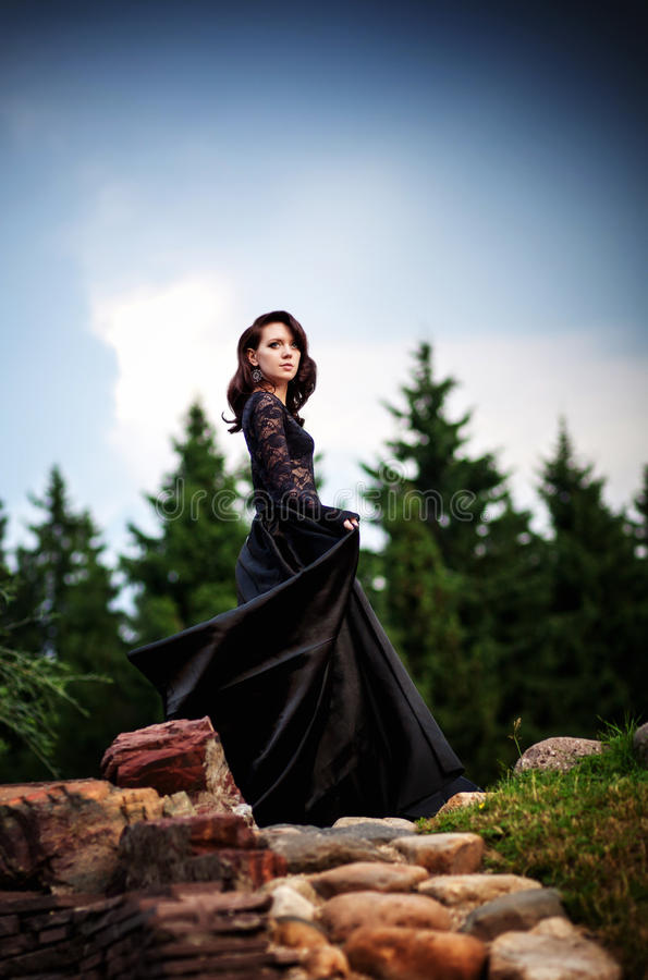 Mystisk flicka i svart klänning från saga royaltyfri bild