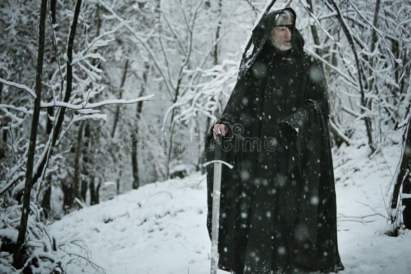 Mystisk gamal man i snöskog royaltyfri fotografi