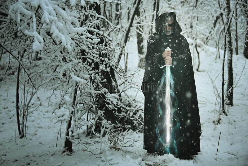 Mystisk gamal man med det magiska issvärdet arkivfoto