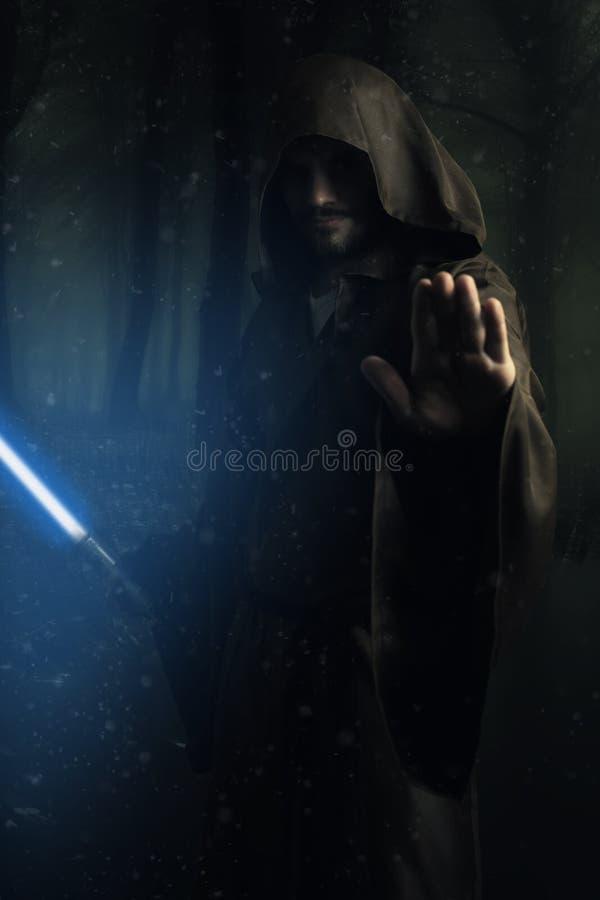 Mystisk krigare som rymmer en lightsaber royaltyfri bild