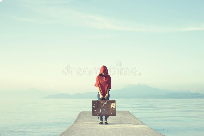 Mystisk kvinna i röda skinn hennes framsida under huven i en förtrollad sjö royaltyfria bilder