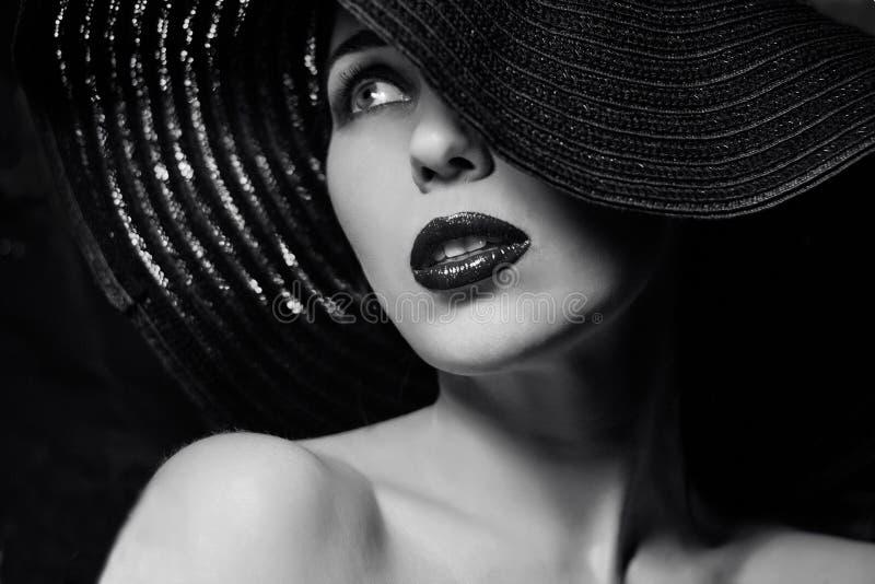 Mystisk kvinna i svart hatt royaltyfria foton