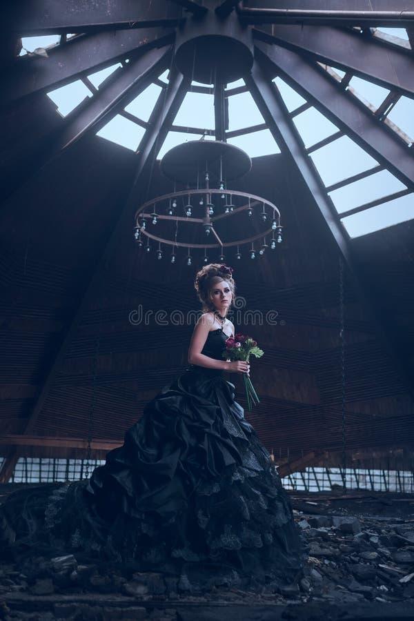 Mystisk kvinna i svart klänning arkivfoton