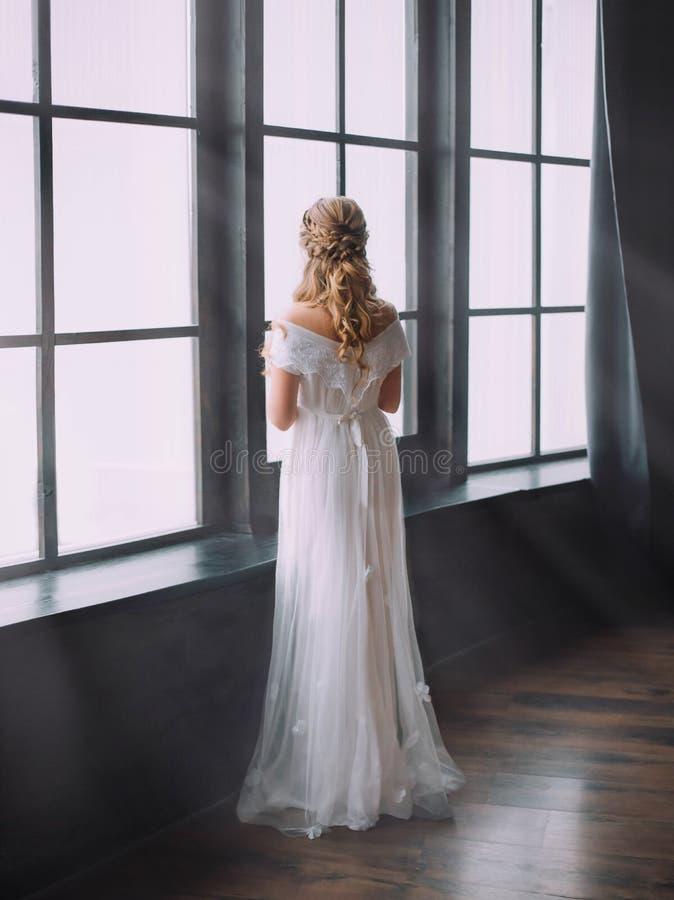 Mystisk kvinna som loking på stora ljusa fönster, förtrollade prinsessavänd in i härlig svan, idérikt väva för royaltyfri foto