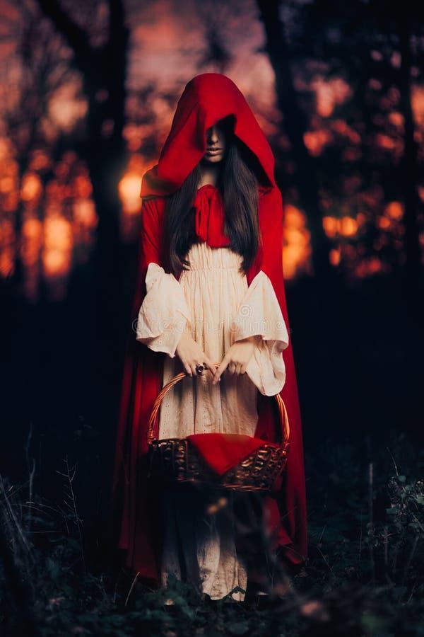Mystisk liten röd ridninghuv i skogen arkivbild
