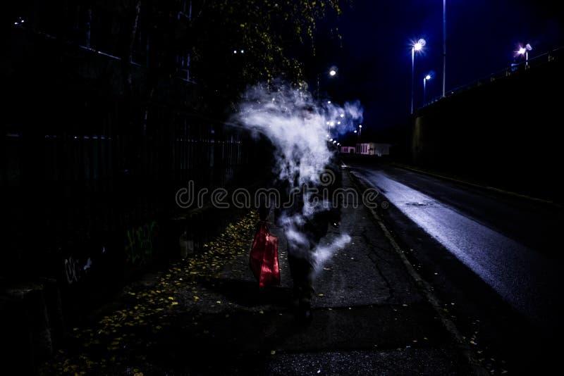Mystisk man som utandas vaping rök som döljer dess framsida, medan gå på gatan under nattetid royaltyfri bild