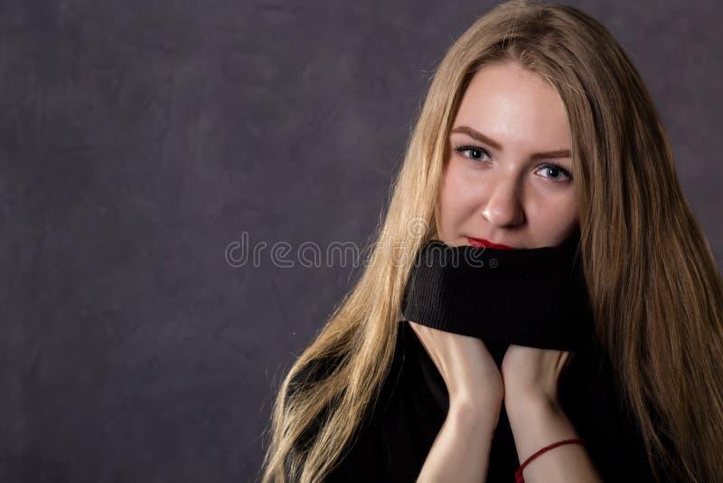Mystisk nätt blond kvinna som bär den svarta stack tröjan Melankolisk och höstbegrepp p? en gr? f?rgbakgrund royaltyfri foto