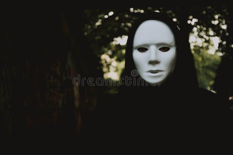 Mystisk person i en vit framsidamaskering som går i träna royaltyfri fotografi